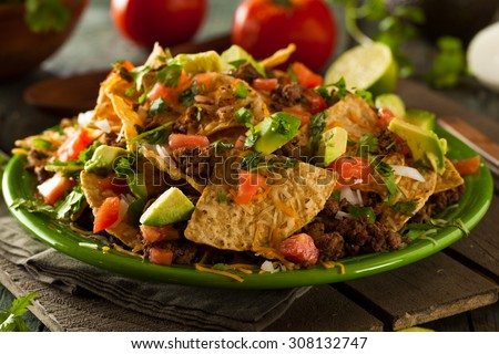 Loaded Beef and Cheese Nachos with Cilantro and Lime - stock photo