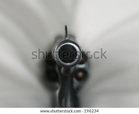loaded gun aiming at viewer - stock photo