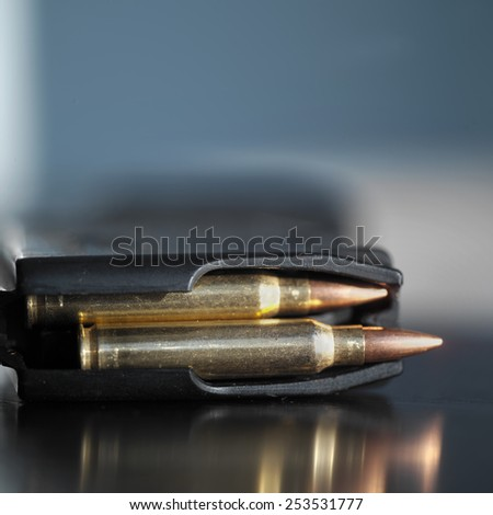 Loaded gun clip bullets in automatic clip, close up with shallow depth of field - stock photo