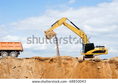Loader Excavator loading body of a dump truck tipper at open cast over blue sky in summer - stock photo