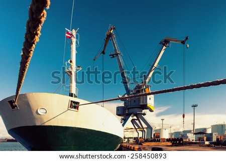 Loading and unloading of rolled iron in the port with cranes in Europe - stock photo