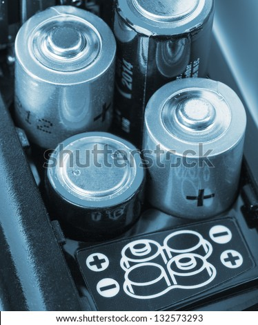 Loading batteries into a electronic device. Toned in blue - stock photo