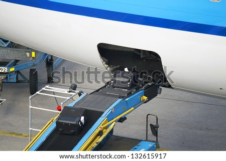 Loading conveyor to a plane - stock photo