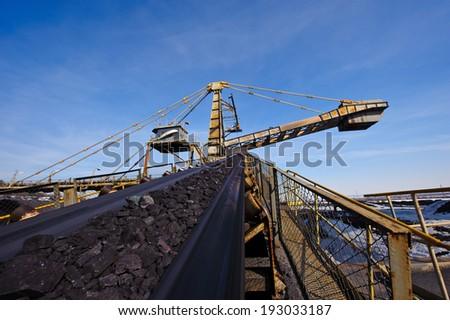 loading iron ore conveyor machine from the warehouse, mining production - stock photo