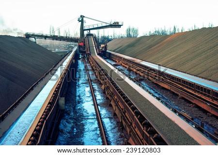 loading iron ore conveyor machine from the warehouse, mining production - stock photo