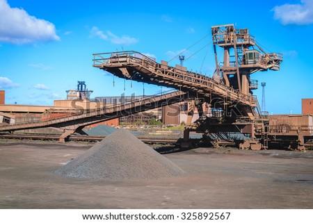 Loading iron ore conveyor machine in steel industry - stock photo