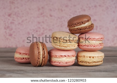 loads of macaroons on a wooden table with a pink background - stock photo