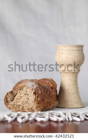 Loaf of bread and chalice with wine. Shallow dof, copy space - stock photo
