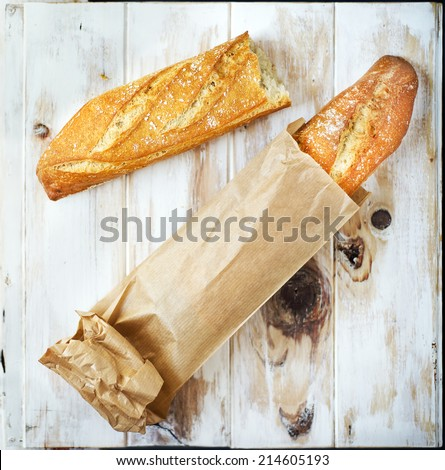 Loaf of bread in a grocey paper bag (european style) on a rustic table. - stock photo