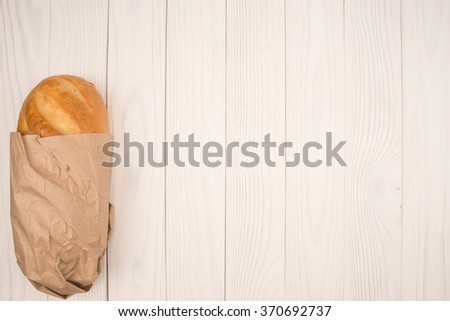 Loaf of bread on a wooden white table. Top view - stock photo