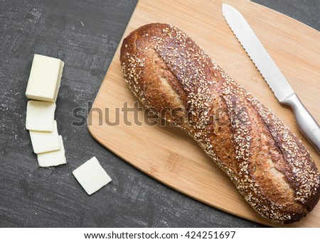 Loaf of dark whole grain bread on wooden bamboo board with knife and sliced butter on a textured slate gray background. - stock photo