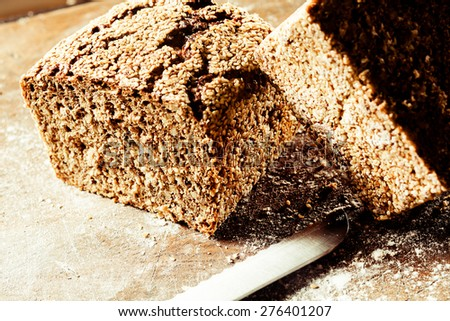 Loaf of delicious freshly baked crusty wholegrain brown bread cut through the center to reveal the texture on a wooden cutting board , close up view - stock photo