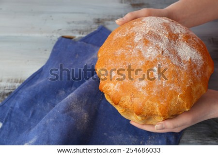 Loaf of freshly bread in female hands with napkin on color wooden table background - stock photo