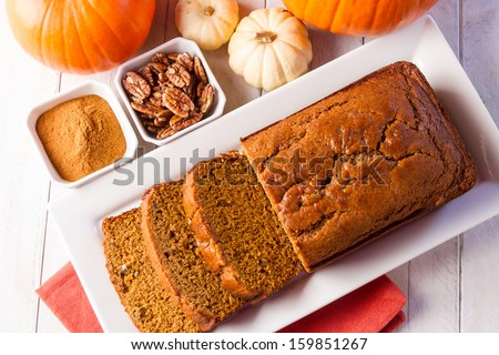 Loaf of pecan pumpkin bread sitting on white plate with orange napkin, spices and assorted pumpkins - stock photo