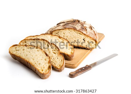 Loaf of rustic bread sliced on cutting board isolated on white background - stock photo