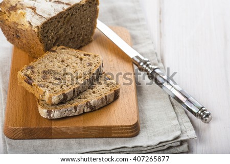Loaf of rye bread and a pair of  slices cut with a knife - stock photo