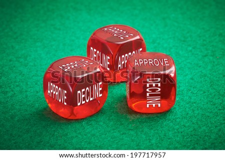 Loan approval concept, three red dice on a green felt background. - stock photo