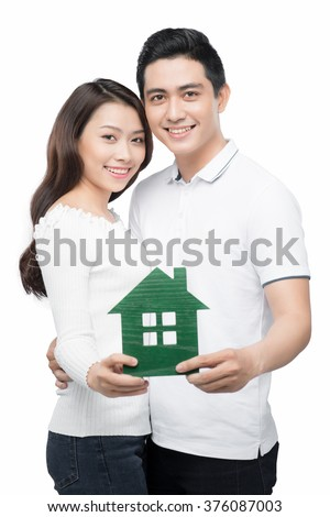 Loan concept. Young couple holding a white miniature house - stock photo