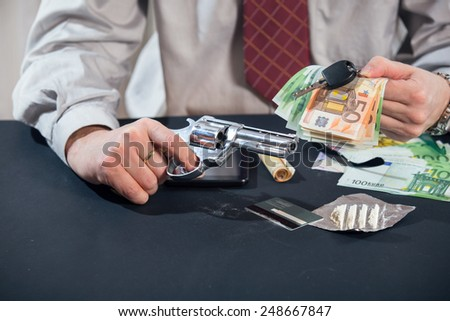 Loan shark with gun, money, drugs - stock photo