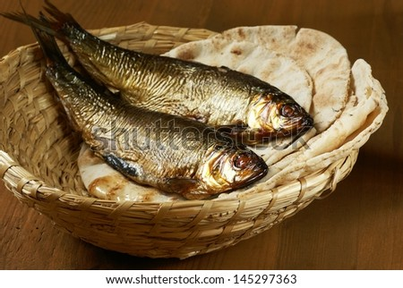 Loaves of bread and two fishes in a basket. - stock photo