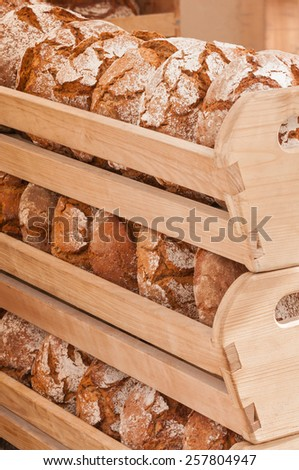 Loaves of crusty bread on wooden shelves, bakery - stock photo