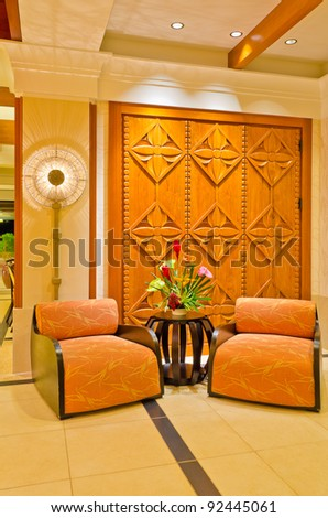 Lobby interior of a hotel with armchairs and flowers - stock photo