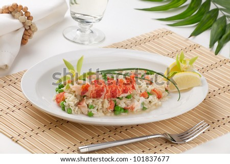 Lobster and green pea Risotto garnished with chives, lemon, and orchid flower. - stock photo