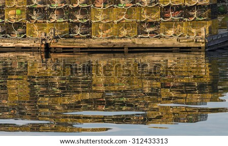 Lobster pots on dock with reflections in Maine harbor. - stock photo