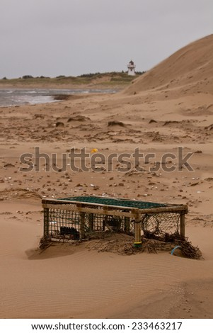 Lobster trap stuck in the shifting blowing sand, Prince Edward Island National Park, on the north shore of Prince Edward Island, Canada - stock photo