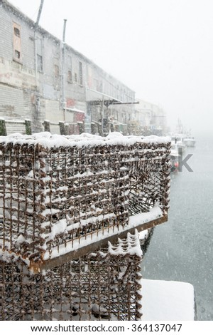 Lobster traps on a pier during a snowstorm in Maine - stock photo