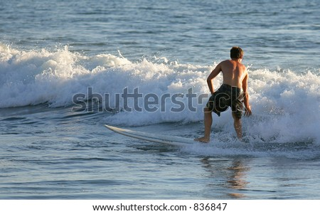 Local boy surfing at sunset - stock photo