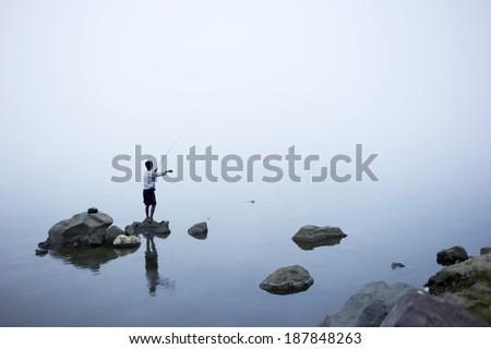 local fishing on misty whether at segara danau anak lake, Mount Rinjani, Lombok, Indonesia  - stock photo