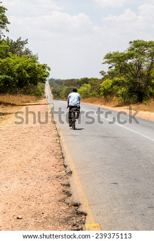 Local man riding on a bike on a desolated road in africa - stock photo