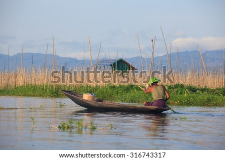 Local people transportation on boat going through a water canal in the floating on the western side of the lake  in Inle Lake,Shan state in Middle of Myanmar. - stock photo
