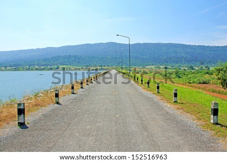 local road beside a dam in mountain - stock photo