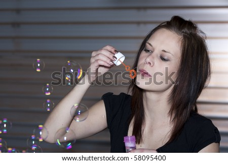 Location shoot of a beautiful young woman blowing bubbles, wearing a black top and standing in front of a garage door. - stock photo