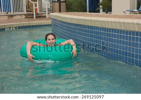 Location shot of a  young girl on a blue/green innertube in a lazy river in Myrtle Beach South Carolina - stock photo