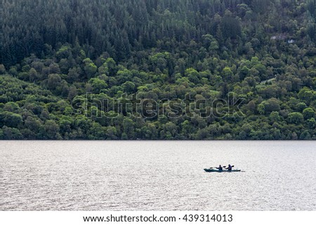 Loch Ness, United Kingdom - August 19, 2014: View of two canoeists in early morning. loch Ness is a large, deep, loch in the Highlands extending for approximately 37 km southwest of Inverness.  - stock photo
