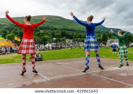 LOCHEARNHEAD, SCOTLAND- JULY, 24,2010: Two girls in traditional dress compete in the sword dance event at Highland Games. - stock photo