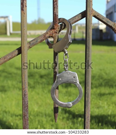 lock in handcuffs to the fence symbolizes captivity - stock photo