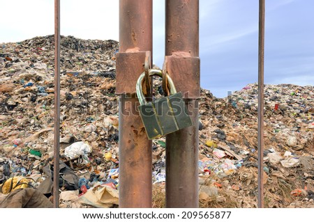 lock key on rusty fence and garbage mountain background - stock photo