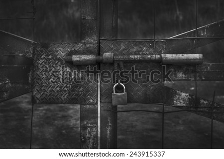 Lock on a chain link security fence in black and  white - stock photo