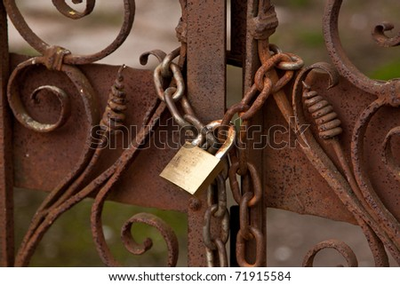 locked chain on old rusty gate - stock photo