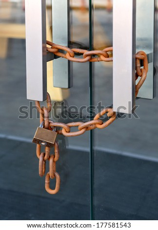 Locked glass door with chain - stock photo