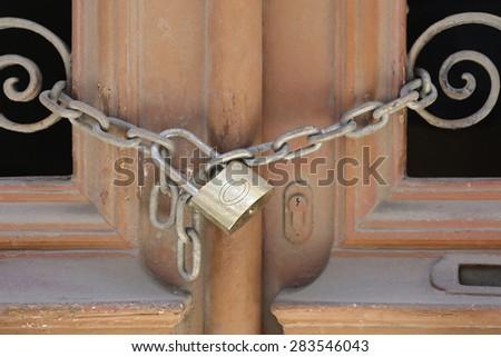 Locked padlock with hain at door - stock photo