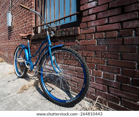 Locked Until You Return.  Blue bicycle against a brick wall, locked and chained to security bars on a window. - stock photo