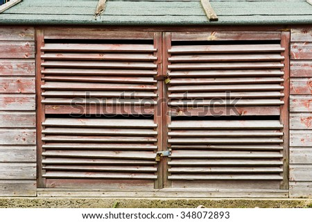 Locked wooden doors of an outside storage container - stock photo
