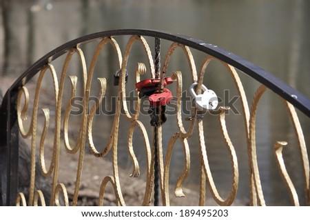 Locks  Suite on the lattice of the bridge over the pond. Hanging locks marriage. - stock photo