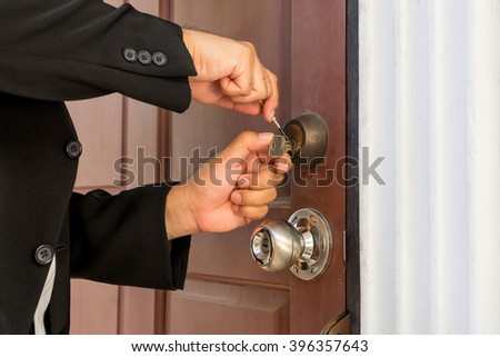 locksmith in black suit repair the lock on wood door - stock photo