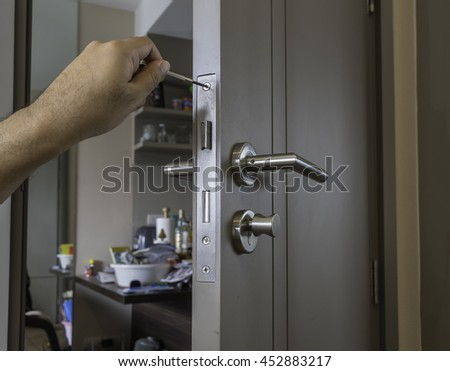 locksmith is repairing the door in room by screwdriver and left hand - stock photo